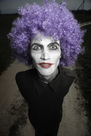 Crazy man outdoors with wig and clown makeup. Artistic darkness and colors added photo