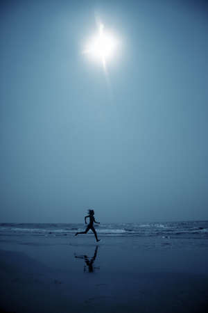 shadowgraph: Woman at the beach running to the water in the deep dark night. Blue color toning added for coolness of the night Stock Photo