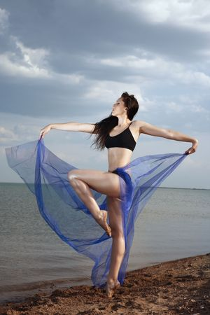nifty: Elegant lady dancing at the beach before rainstorm. Stock Photo