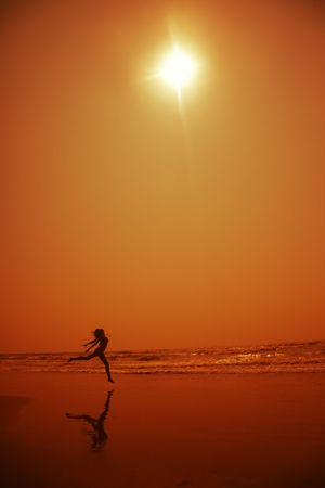 Silhouette of the lady dancing at the beach in deep dark night. Artistic orange colors toning added Stock Photo