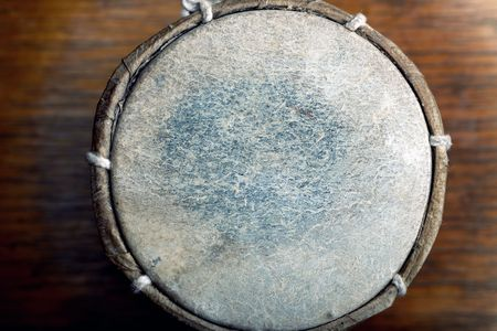 drumming: Old leather drum. Top view on the surface. Horizontal photo with shallow depth of field