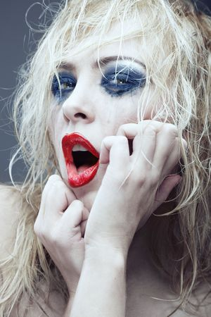 Crazy blond lady with bizarre makeup. Vertical portrait. Artistic colors added photo