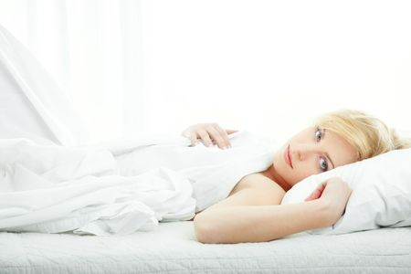 bedstead: Blond lady laying on the bed in a white bedroom. Natural colors Stock Photo