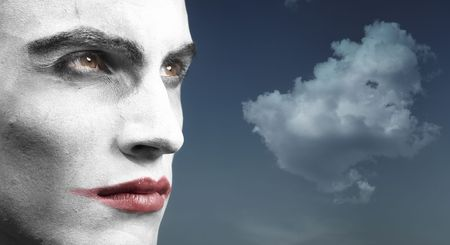 Headshot of the vampyre outdoors and cloud on the background. Artistic colors and darkness added photo
