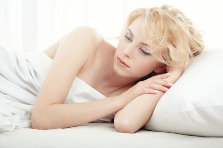 Sad lady indoors laying in the white bedroom at the early morning Stock Photo