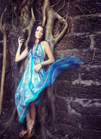 nifty: Elegant lady in the blue dress standing at the old banyan. Goa, India.  Stock Photo