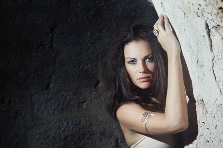 dungeon: Beautiful brunette lady in the stony dungeon. Horizontal photo. Natural darkness and colors