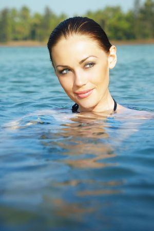exotics: Beautiful lady in the water. Vertical close-up portrait. Artistic colors added