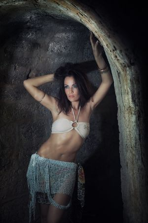 Wild styled lady indoors in the dark stony dungeon. Vertical photo. Artistic darkness added Stock Photo - 7610287