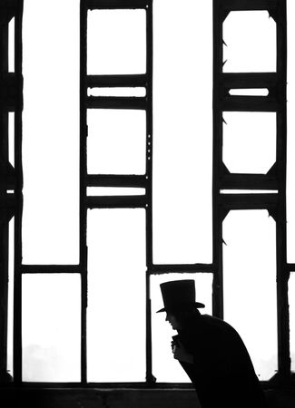 meshed: Silhouette of the Man in the black coat and hat in the dark interior near the meshed window. Monochrome photo