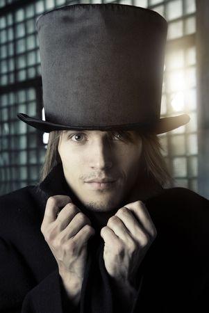 arroganza: Uomo in nero cappotto e cappello. Colori artistici e grano aggiunto  Archivio Fotografico