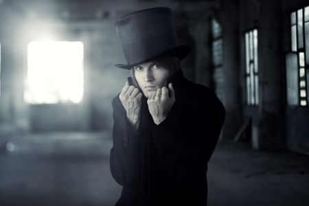 privy: Bad man in the black coat and top hat. Artistic colors and grain added Stock Photo