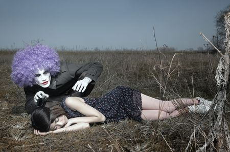 periwig: Sleeping girl outdoors and crazy maniac clown touching her shirt. Artistic colors added Stock Photo