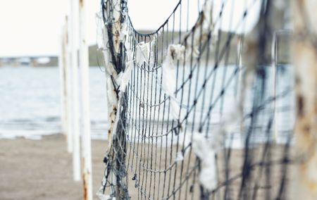fishingnet: Old net attached to the poles at the beach. Shallow depth of field added for more natural view Stock Photo
