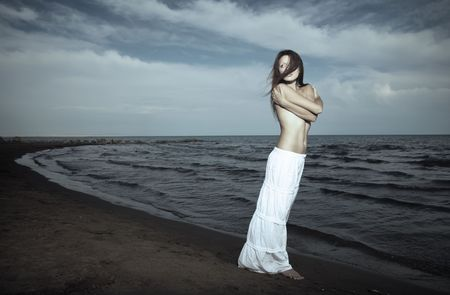 Single topless lady in the white shirt standing near the sea. Hairs are blown by the wind. Artistic colors and darkness added photo