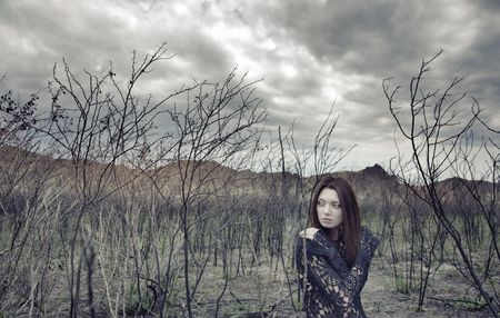Sad alone woman in the dead bushes and thunderous sky on a background. Artistic colors added for movie effect Stock Photo