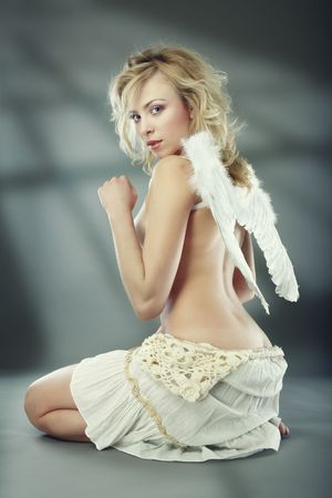 Perfect topless lady with white angelic wings. Shadows on a background. Natural colors