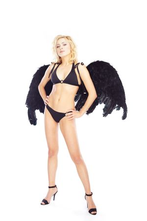 Beautiful blond lady standing akimbo with black artificial angel wings. Studio shot on a white background photo