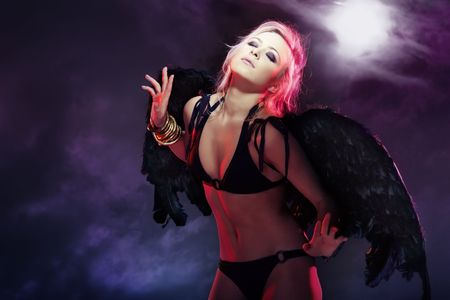 Beautiful blond lady outdoors with black wings. Full moon sky on a background. Artistic colors and darkness added photo