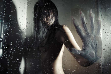 nightmare: Female werewolf in the dark bathroom touching wet glass by his huge hand with sharp nails. Natural darkness. Artistic colors and grain added Stock Photo