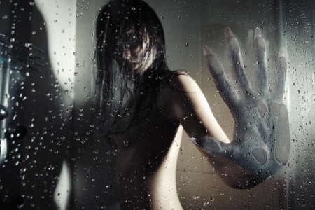 evil girl: Lupo mannaro femmina in bagno scuro toccare il vetro bagnato dalla sua mano enorme con chiodi taglienti. Oscurit� naturale. Colori artistici e granulosit� aggiunta  Archivio Fotografico