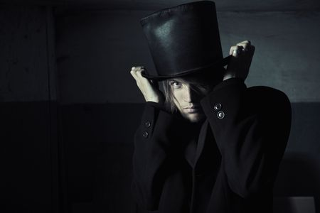 stovepipe hat: Murderer in black coat and top hat in the dark interior. Natural darkness and artistic colors added