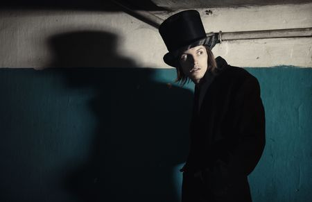 madman: Criminal man in vintage black coat and top hat in the dark interior. Natural darkness and colors