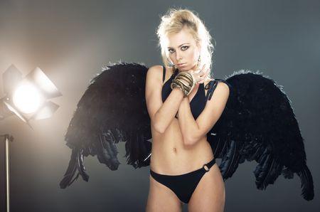 nifty: Blonde vrouw in zwarte lingerie met engel vleugels poseren in de studio. Licht apparatuur werkt op de achtergrond  Stockfoto