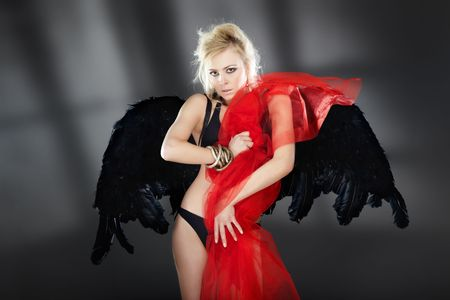 Sexy blond lady with black angel wings holding red bloody fiber in the dark interior with shadows photo