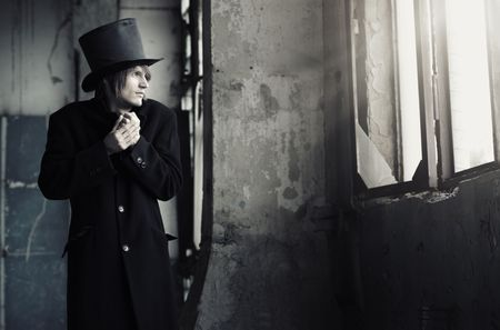 Man in vintage black coat and top hat indoors looking to the window. Artistc colors added photo