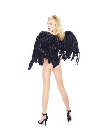Rear view on the turning back lady in lingerie with black angel wings. White background photo