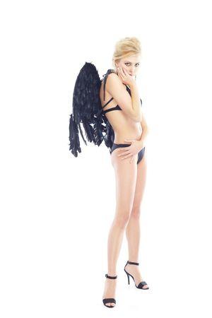 Beautiful blond lady with black artificial angel wings. Studio shot on a white background photo