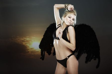 Sexy lady in the lingerie with black angelic wings on a defocused sky background. Natural colors photo