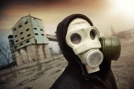 atomo: Hombre de la m�scara protectora de gas cerca de la planta industrial durante el atardecer radiactivo. Colores art�sticas y granulado agregado