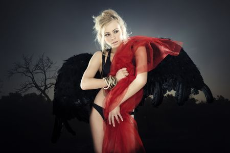 Blond female angel with black wings standing outdoors and holding bloody fiber during dark night. Artistic colors and grain added photo