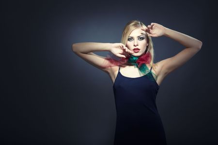 Elegant blond lady in stylish dress and colorful scarf posing in the studio on a dark background photo