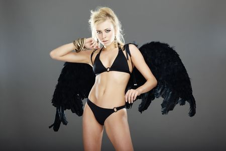succubus: Blond female angel with black wings on a dark gray background