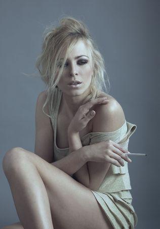 Sad woman indoors smoking cigarette Stock Photo - 7872499