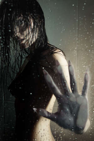 Female witch standing in the shower room behind the wet glass. Artistic darkness and texture added photo