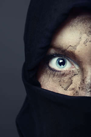 Half face of the human in black hood with damaged skin. Artistic colors and painting added photo