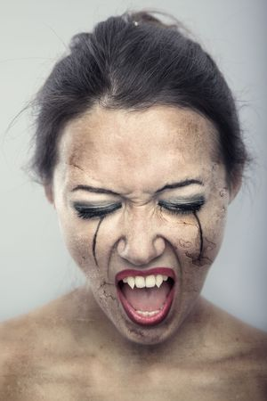 Female vampire with burnt skin on a gray background. Artistic colors added photo