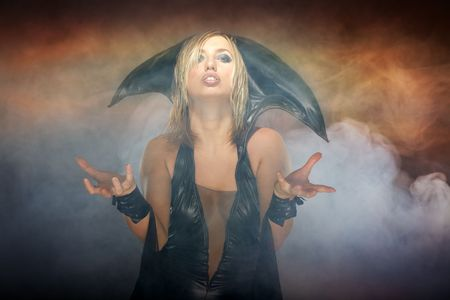 succubus: Blond lady in Halloween witch costume on the smoky hell background. Natural smoke was produced by smoking machine Stock Photo