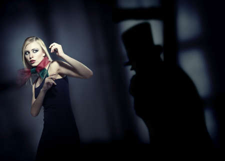 Blond afraid lady in the dark interior with deep shadows. Artistic colors and grain added Stock Photo - 8016269