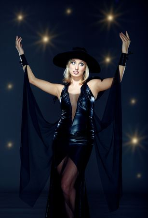 succubus: Good sorceress in black dress and hat at the dark background with stars Stock Photo