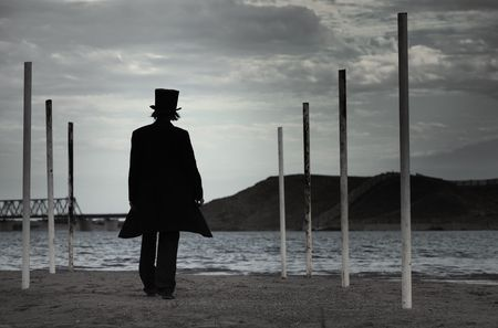shadowgraph: Rear view on alone man in the black coat and top-hat going to the sea. Natural darkness. Artistic colors added Stock Photo