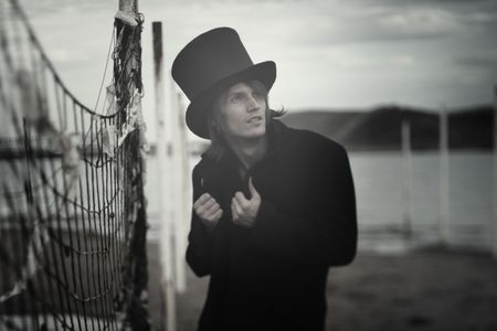Man in vintage black coat and top hat outdoors. Artistic colors added. Natural light and darkness. Shallow depth of field added for artistic view photo