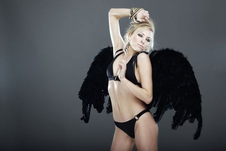Blond female angel with black angel wings on a dark gray background photo