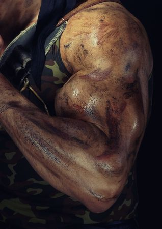Close-up photo of the muscular hand with dirty skin of the strong warrior. Natural colors and darkness