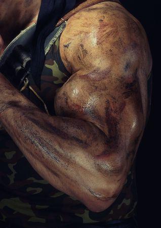 guerrero: Foto de primer plano de la mano muscular con la piel sucia del guerrero fuerte. Colores naturales y de la oscuridad