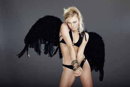 Sexy blond lady in the lingerie with black angel wings on a dark background photo